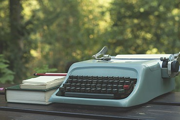 old typewriter on a wooden garden table with books
